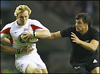 Daniel Carter prepares to tackle England's Lewis Moody