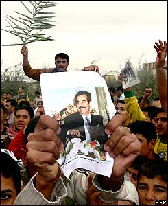A supporter holds a picture of ousted Iraqi dictator Saddam Hussein during a demonstration in Samarra