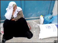 A woman in Beit Hanoun sits by a sack of food