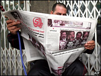 Iraqi reads newspaper as curfew is lifted in Baghdad