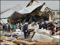 Firefighters and other rescuers shift through the rubble after a tornado hit the town of Saroma  - 7/11/06
