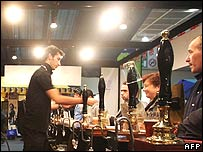 Man serving beer to drinkers at a bar