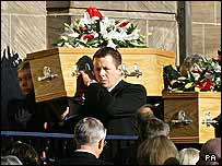 Neil Shepherd [left] and Paul Wood carry one of the coffins