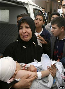 Palestinian woman carries an injured child