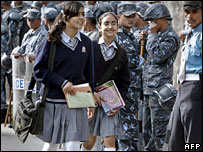 Nepalese school girls walking past security forces