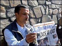 Nepalese man holds up a newspaper headlining the peace deal