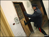 An Italian policeman breaks down a door during a raid in Naples