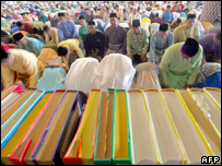 Malaysian muslims pray behind of the Koran during a special morning prayer at the National Mosque in Kuala Lumpur