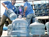 Labourers unload water bottles in Jakarta