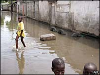 Child wades through standing water in Senegal