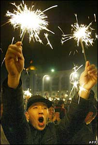 Kyrgyz opposition supporters celebrate near the parliament building in Bishkek