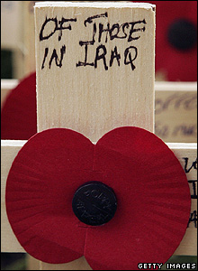 A wooden cross and a poppy
