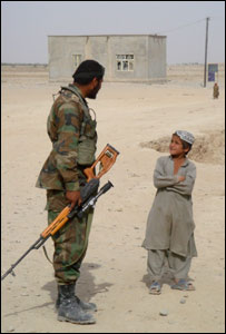 A soldier talks to an Afghan child