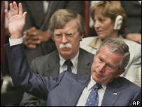 George W Bush lifts his hand to vote as John Bolton looks on