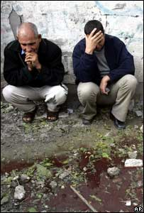Palestinians sit next to a pool of water stained with blood