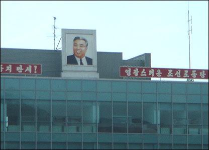 Retrato del difunto l�der Kim Il Sung y consignas de alabanza