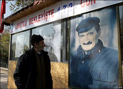 A man next to a portrait of Bulent Ecevit
