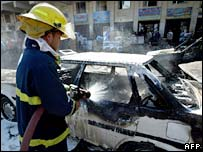 Fireman douses car damaged in Baghdad blasts