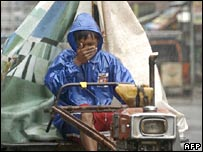 A rain-lashed farmer drives a utility vehicle in Pangasinan province, the Phillippines