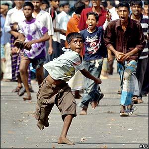 A Bangladeshi boy hurls a stone at police