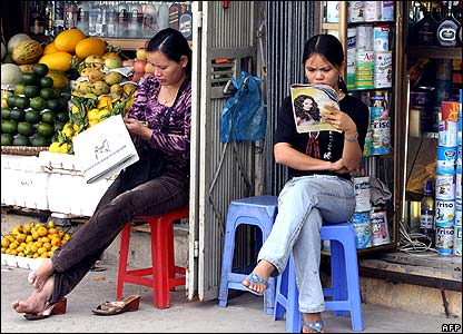 Shopkeepers reading newspapers outside shops