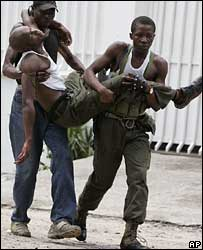 Troops loyal to Mr Bemba carry a wounded colleague