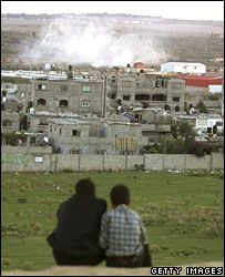 Palestinian boys watch smoke rising from Beit Hanoun