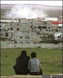 Palestinian boys watch smoke rising from Beit Hanoun