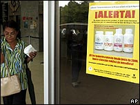 A woman passes near a poster warning about contaminated medicine in Panama
