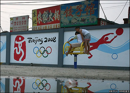 Children play in front of Olympic poster boards in Beijing