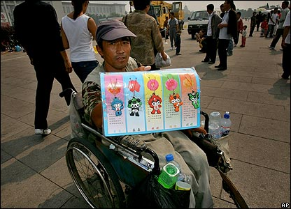 A Chinese man in a wheelchair sells Olympic mascots in Tiananmen Square in September 2006