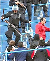 Policías persiguen a hinchas de Chacarita Juniors en las tribunas del estadio de Boca Juniors.