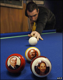 A man plays pool with balls featuring the French Socialist presidential candidates