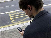 A man watches TV on his mobile while waiting for a bus