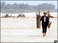 A farmer walks along the dried-up bed of the Beijiang River in Qingyuan City, China