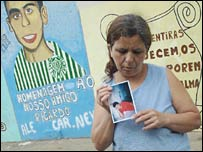 Iracy Flauzino holds a photograph of her son Ricardo in front of a mural in homage to him