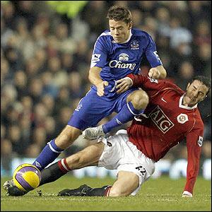 Everton's James Beattie feels the force of John O'Shea's crunching tackle
