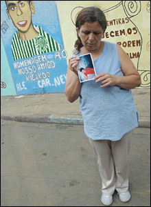 "Ricardo's mother holds his photo in front of a mural that reads ""In homage to our friend Ricardo"""