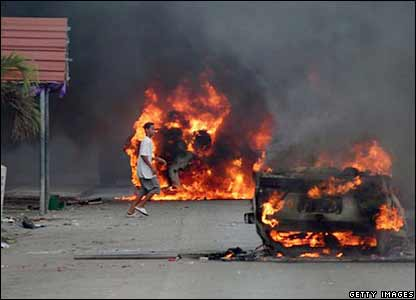 A man walks past burning vehicles in Nuku'alofa. Picture: 17 November 2006