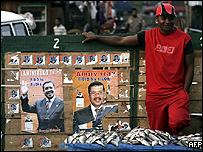 Fishmongers sit next to their stall along Malagasy opposition leaders electoral posters