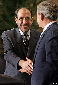 Mr Maliki (left) takes Mr Bush's hand