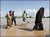 Kenyans walk through flood waters