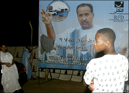 Mauritanian in front of campaign poster