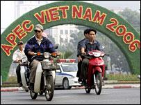 Motorcyclists pass an Apec floral banner in Hanoi, Vietnam