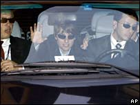 Tom Cruise waves to the crowd as he is driven through the castle gates