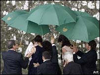 Bodyguards hold umbrellas as Katie Holmes arrives at the castle ahead of the wedding