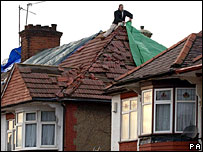A man attempts to repair a roof