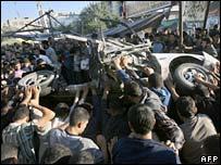 Palestinians gather around a destroyed car in Gaza