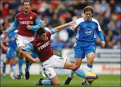 Wigan's Kevin Kilbane (r) is tackled by Villa defender Gareth Barry