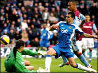 Aston Villa goalkeeper Thomas Sorensen denies Wigan's Paul Scharner early in the second half